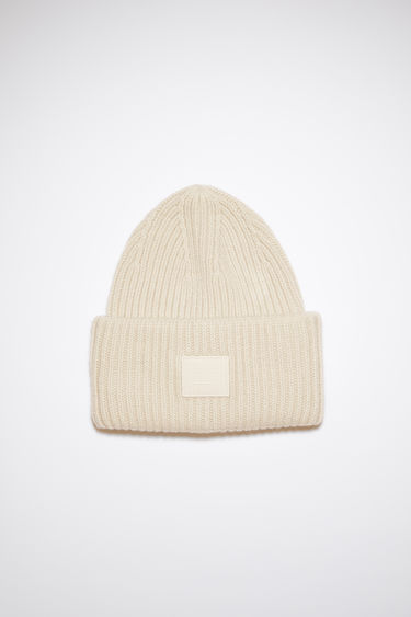 Acne Studios cream beige beanie hat is made from rib knit wool with a face logo patch.
