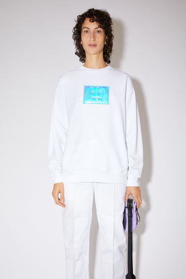 Acne Studios optic white oversized sweatshirt is made of organic cotton with a metallic face logo print and ribbed details.