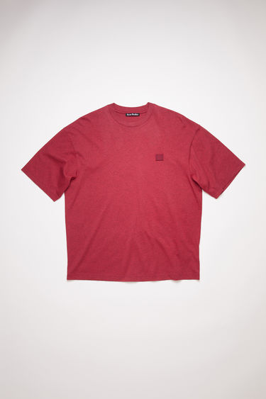 Acne Studios deep red relaxed fit t-shirt is made of organic cotton with a ribbed crew neck and face logo patch.