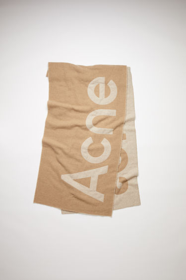 Acne Studios oatmeal/beige oversized scarf is made of a soft recycled wool blend featuring bold, contrasting logo lettering on both sides.