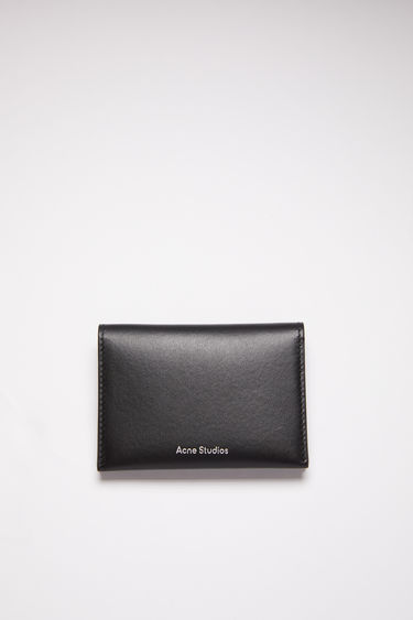 Acne Studios black bifold card holder is made of soft grained leather with four card slots and a silver stamped logo on the front.