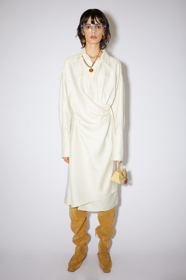 Acne Studios warm white fluid shirt dress is made of shantung and features an asymmetrical button placket.