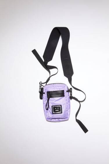 Acne Studios lilac purple pocket bag is made from technical ripstop with a detachable crossbody strap and an array of zipper and mesh pockets, accented with a polished metal logo plaque with a face motif in black.