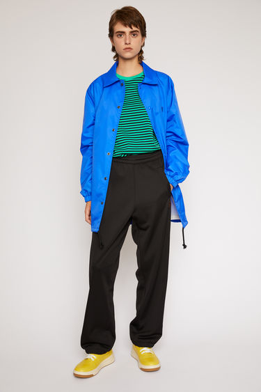 Acne Studios black lounge pants are crafted from technical jersey with an elasticated drawstring waist and trimmed with contrasting stripes down the sides.