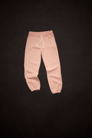 Acne Studios powder pink organic cotton sweatpants feature an elastic drawstring waist and tonal embroidered face patch on the front.