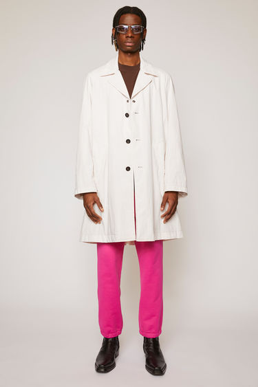 Acne Studios warm white trench coat is crafted from washed cotton to an A-line silhouette and finished with two side slip pockets and tonal buttons down the front.