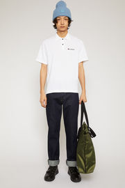 Acne Studios optic white polo shirt is crafted from lightweight cotton pique with a point collar and two-button placket and features a twill logo-embroidered patch on the chest.
