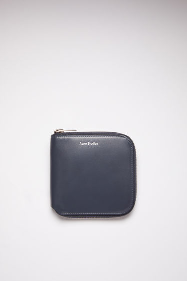 Acne Studios dark blue medium-sized leather wallet has compartments for cards, coins, and documents.