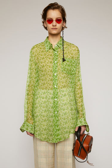 Acne Studios fern green blouse is crafted from crinkled silk chiffon and patterned with a floral print reminiscent of vintage wallpapers. It's cut to a relaxed fit with a point collar and an asymmetric shirttail hem.