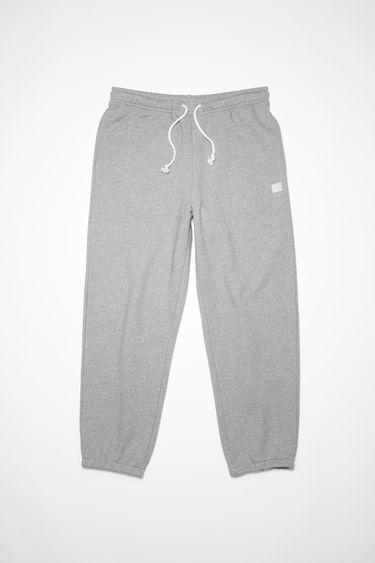 Acne Studios light grey melange organic cotton sweatpants feature an elastic drawstring waist and tonal embroidered face patch on the front.
