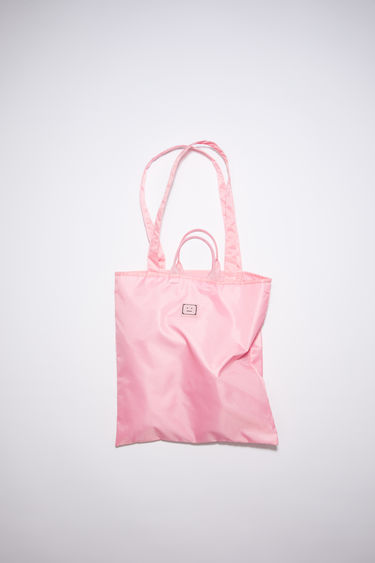 Acne Studios bright pink tote bag is made from recycled polyester, featuring both carrying handles and shoulder straps. It has a mesh-lined interior pocket and tonal metal logo plaque.
