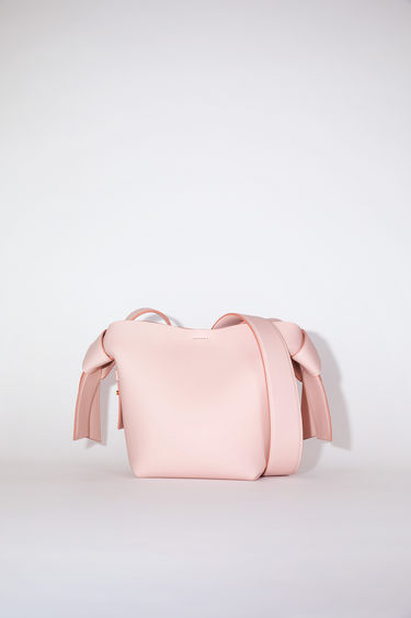 Acne Studios rose pink small bag features twisted knots inspired by traditional Japanese obi sashes. It has a debossed logo and snap button closure, which opens to reveal a zipper compartment for storing small essentials.