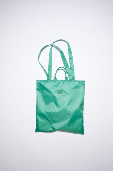 Acne Studios jade green tote bag is made from recycled polyester, featuring both carrying handles and shoulder straps. It has a mesh-lined interior pocket and tonal metal logo plaque.