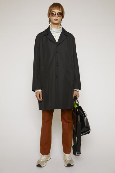 Acne Studios black trench coat is crafted to an A-line silhouette and finished with two side slip pockets and tonal buttons down the front.