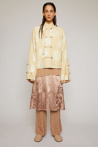 Acne Studios cream beige jacket is crafted from cotton-canvas and patterned with a rose motif. It's shaped to a boxy fit with a stand collar and accented with knots and button closures.