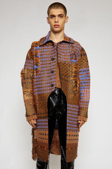 Acne Studios multi blue coat is woven with wool and straw-effect threads and features an abstract pattern of pixelated glitches. It's intentionally distressed and has a curved cutaway on the front.