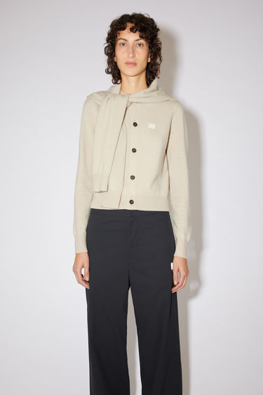 Acne Studios cream beige crew neck cardigan sweater is made from wool with a face logo patch and ribbed details.