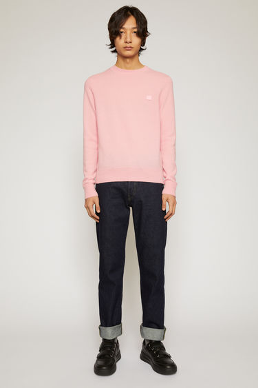 Acne Studios blush pink sweater is knitted in a fine gauge from soft wool yarns and accented with a tonal face-embroidered patch on the chest.