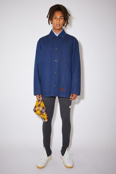 Acne Studios indigo blue unlined workwear jacket is made of soft indigo denim with a face logo patch.