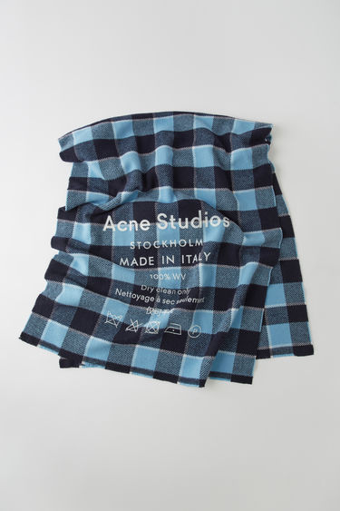 Acne Studios navy/dusty blue scarf is patterned with a check design and features a screen printed Acne Studios logo and care label.