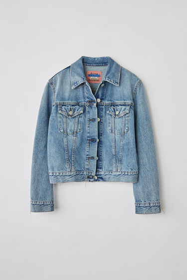 Acne Studios 1999 Light Blue Trash denim jacket is crafted from rigid denim with a light stone wash. It is finished with chest flap pockets and untrimmed button holes.