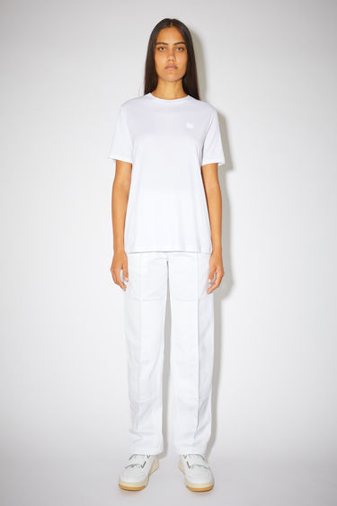 Acne Studios optic white t-shirt is crafted from lightweight cotton jersey to a slim-fitting silhouette with a round neckline and accented with a tonal face patch on the chest.