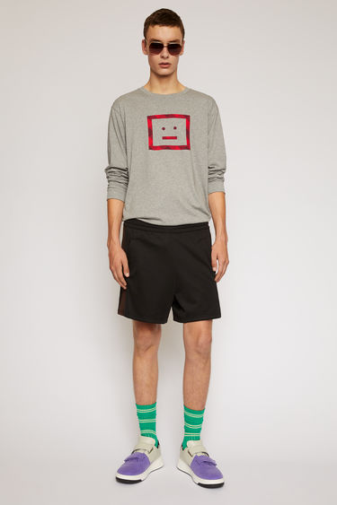 Acne Studios black track shorts are crafted from technical jersey with an elasticated drawstring waist and trimmed with contrasting stripes down the sides.