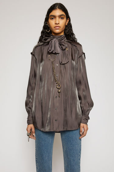 Acne Studios chestnut brown blouse is crafted from crinkled satin that has lustrous sheen finish. It's cut to a fluid drape with a tie at the neck and finished with jagged edges for a subtle note of texture.