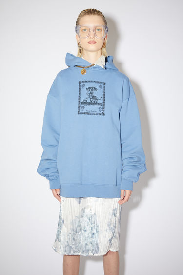 Acne Studios denim blue oversized hooded sweatshirt is made of organic cotton with a printed design on the front.