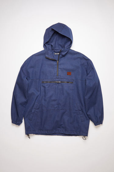 Acne Studios indigo blue hooded anorak jacket is made of a soft indigo denim with retro styling.