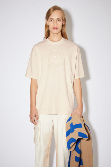 Acne Studios coconut white crew neck t-shirt is made of cotton with an embroidered logo design on the front.