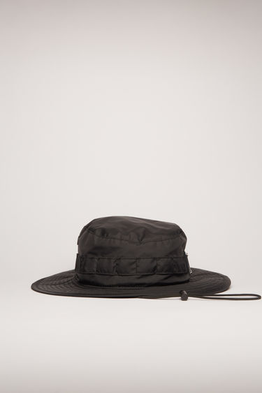 Acne Studios black nylon bucket hat is crafted with a flat-topped crown and a quilted brim and features metal eyelet vents, elastic drawstring and a metal logo plaque.