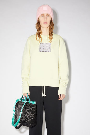 Acne Studios gold regular fit crew neck sweatshirt features a beaded face detail on the front.