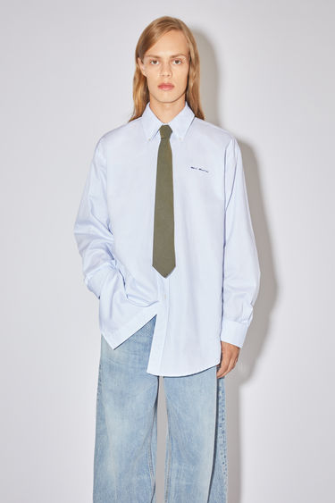 Acne Studios white/blue long sleeve shirt is made of subtly checked cotton with a logo at the chest.