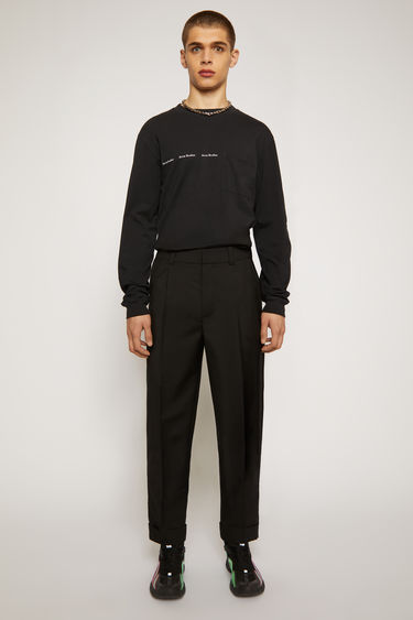 Acne Studios black trousers are made from lightweight cotton twill and cut to a cropped, tapered leg and neatly finished with front pleats and cuffed hems.
