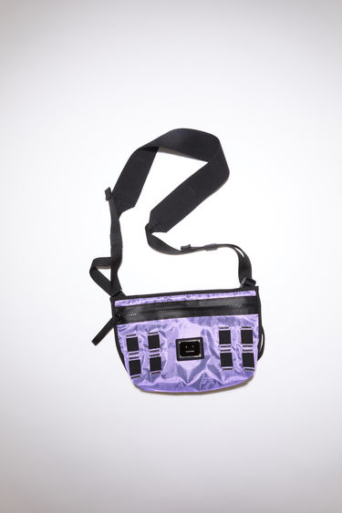 Acne Studios lilac purple crossbody bag is made from technical ripstop and features a silver-tone metal logo plaque with a face motif in black. It has a front zipper pocket, mesh pocket, and an adjustable buckle strap.