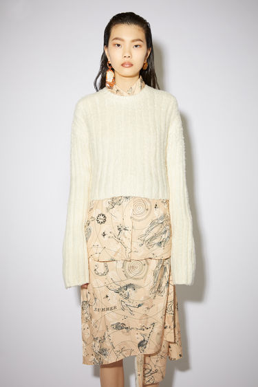 Acne Studios cream beige crew neck sweater is made of a fluffy, brushed cotton blend with a cropped fit.