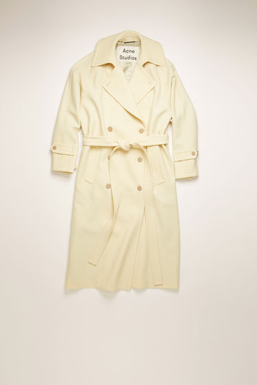 Acne Studios cream beige trench coat is crafted from wool-twill with raglan sleeves and an oversized back storm flap and accented with thick topstitching and whipstitched buttons.