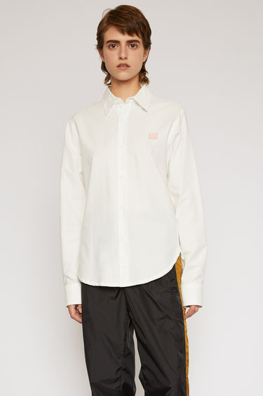 Acne Studios white shirt is shaped to a slim silhouette with a curved hem and accented with a light pink face patch on the chest.