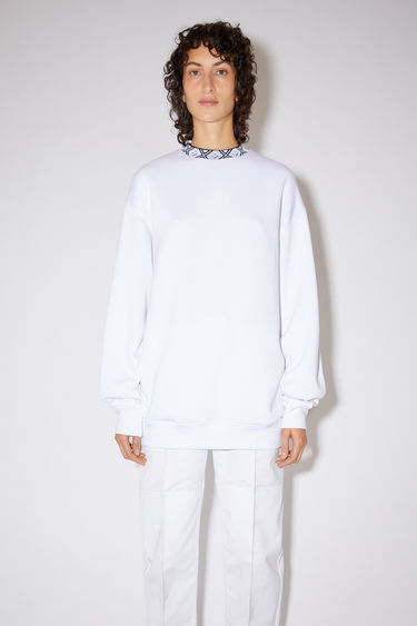 Acne Studios optic white sweatshirt is crafted from midweight brushed jersey to an oversized fit and features a ribbed mock neck inlaid with a face-jacquard design.