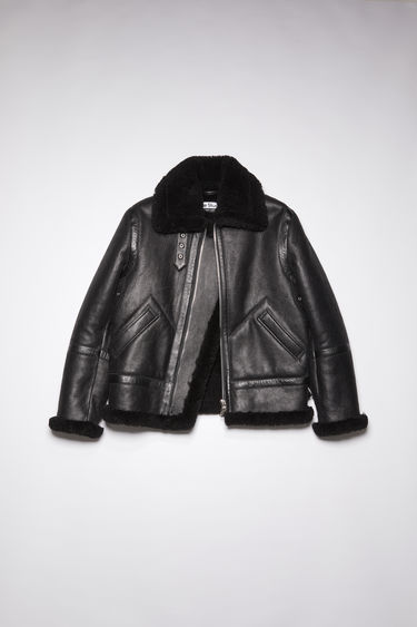 Acne Studios black aviator jacket is crafted from soft, grain leather and lined with shearling for optimum warmth. It's shaped with a wide collar and has classic features such as a throat latch, adjustable side buckles and a two-way front zip fastening.