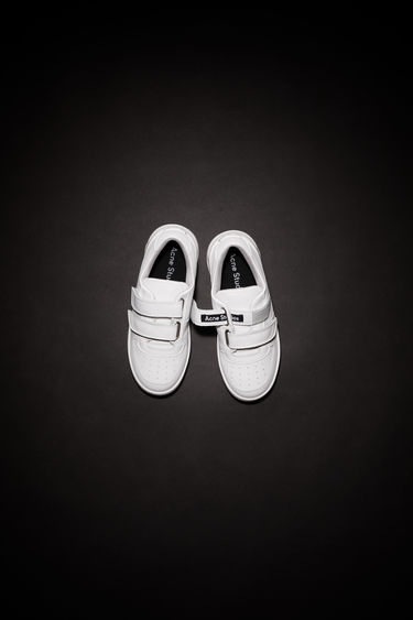 Acne Studios Mini Steffey white/optic white sneakers are crafted from calf leather to a round toe silhouette with velcro strap closures and accented with a face motif on the back of the sole.
