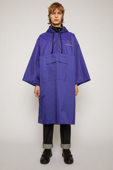 Acne Studios sea blue poncho is crafted from technical shell fabric to an oversized silhouette with a drawstring hood and front patch pocket and features a reflective logo-print across the chest.