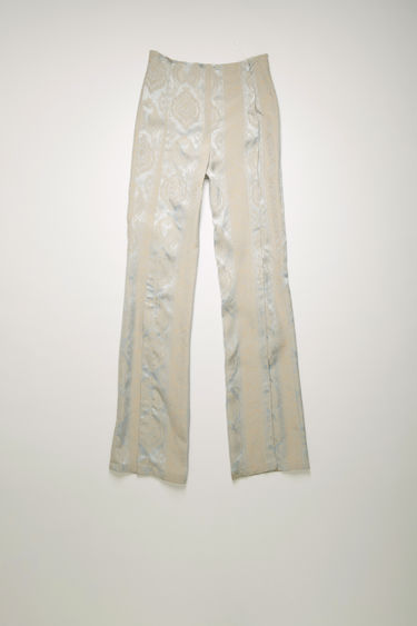 Acne Studios blue/cream trousers are crafted from satin viscose that's jacquard woven with a paisley pattern and are cut to flared, slim-fitting legs with neat, stitched folds through the front.