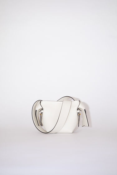 Acne Studios white/black small bag features twisted knots inspired by traditional Japanese obi sashes. It has a debossed logo, magnetic closure, and detachable strap with handles for wear as either a shoulder or handbag.