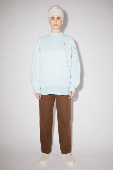 Acne Studios powder blue relaxed bubble fit sweatshirt is made of organic cotton with a contrasting face patch and embroidery.
