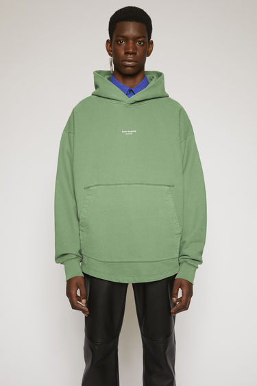 Acne Studios bottle green hooded sweatshirt is made from brushed cotton jersey that's been garment dyed for a soft, washed-out finish and features a reversed logo purposely printed imprecisely across the front.