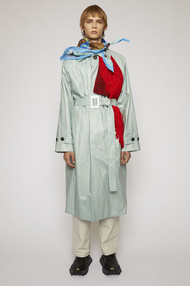 Acne Studios cold grey trench coat is crafted from a technical ramie-voile with a detachable belt and features a contrasting storm flap with long fringed trims.