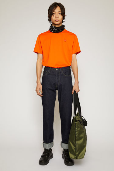 Acne Studios indigo blue jeans are crafted from rigid denim to a high-rise silhouette with straight legs and accented with white topstitching and a face-embroidered patch on the back pocket.