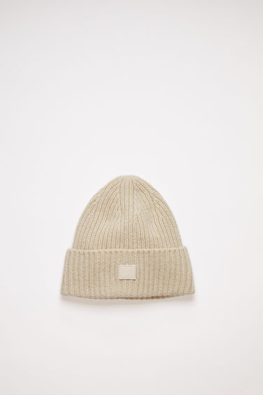 Acne Studios children's cream beige hat is made from rib knit wool with a face logo patch.